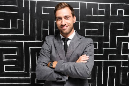 Photo for Handsome and smiling businessman in suit with crossed arms standing near labyrinth - Royalty Free Image