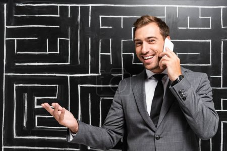 Photo for Handsome and smiling businessman in suit talking on smartphone and standing near labyrinth - Royalty Free Image