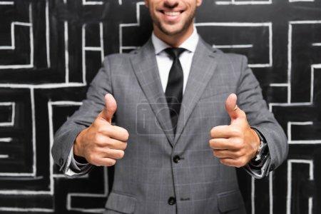 Photo pour Vue recadrée d'un homme d'affaires souriant en costume montrant les pouces près du labyrinthe - image libre de droit