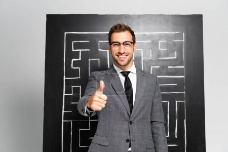 Photo for Handsome and smiling businessman in suit showing like and standing near labyrinth - Royalty Free Image