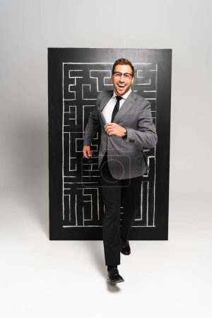 Foto de Un empresario guapo y sonriente en traje que corre cerca del laberinto. - Imagen libre de derechos