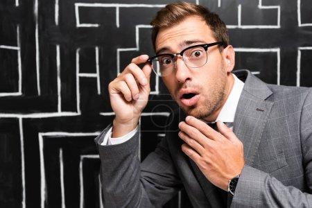 Photo pour Beau et choqué homme d'affaires en costume regardant la caméra près du labyrinthe - image libre de droit