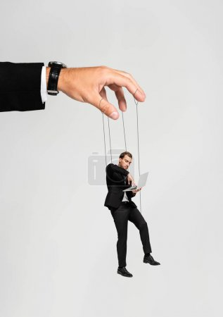 cropped view of businessman playing with marionette with laptop isolated on grey