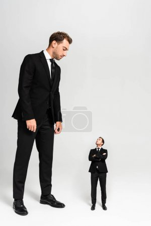 Photo pour Homme d'affaires en costume regardant une marionnette aux bras croisés sur fond gris - image libre de droit