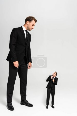 businessman in suit looking at frightened marionette on grey background