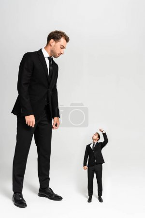 Photo for Businessman in suit looking at marionette showing fist on grey background - Royalty Free Image