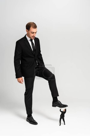 angry businessman in suit stepping on frightened marionette on grey background
