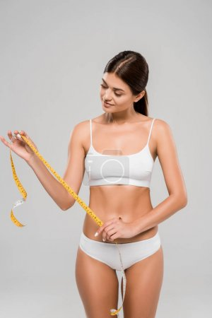 Photo for Smiling beautiful slim woman in underwear holding measuring tape on waist isolated on grey - Royalty Free Image