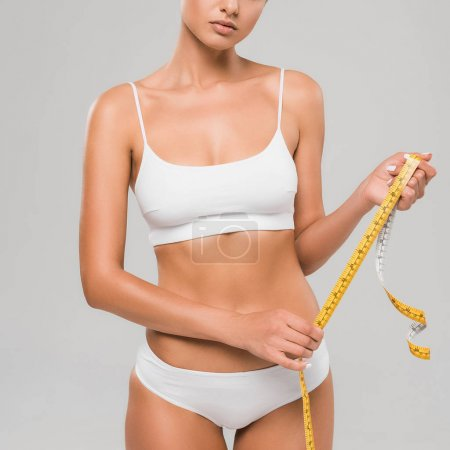 Photo for Partial view of beautiful slim woman in underwear holding measuring tape isolated on grey - Royalty Free Image