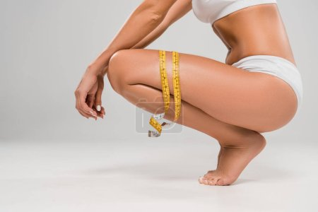 Foto de Cropped view of beautiful slim woman in underwear sitting on tiptoe with measuring tape on grey background - Imagen libre de derechos