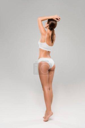 full length view of beautiful slim woman in underwear posing on tiptoe on grey background