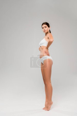 Photo pour Full length view of beautiful slim woman in underwear posing on tiptoe on grey - image libre de droit
