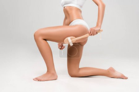 Photo for Cropped view of slim woman in underwear massaging legs with wooden massage brush isolated on grey - Royalty Free Image