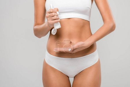 cropped view of slim woman in underwear squeezing lotion isolated on grey