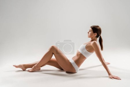 Photo for Side view of beautiful slim woman in underwear sitting on grey background - Royalty Free Image