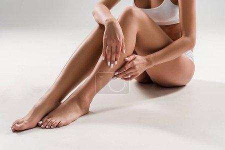 Photo pour Vue recadrée de belle femme mince levant les jambes sur fond gris - image libre de droit