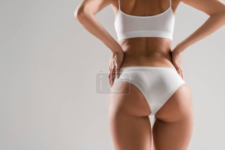 Photo for Back view of beautiful slim woman in underwear with hands on hips isolated on grey - Royalty Free Image