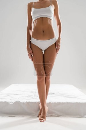 partial view of beautiful slim woman in underwear standing near bed on tiptoe isolated on grey