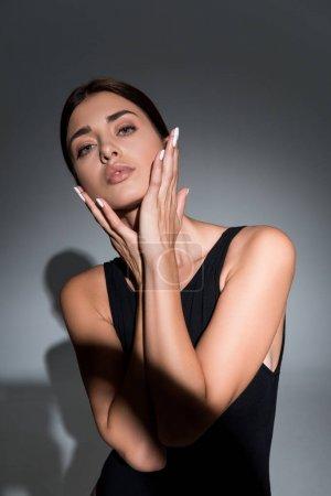 Photo pour Beau modèle jeune posant avec les mains près du visage sur fond noir - image libre de droit