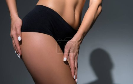 Photo for Cropped view of beautiful slim woman in underwear touching leg on black background - Royalty Free Image