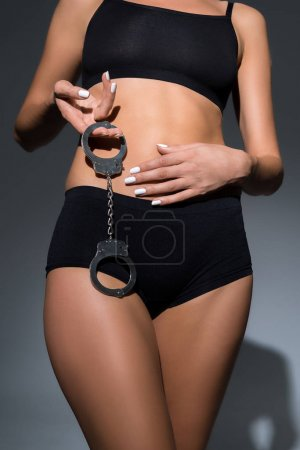 Photo for Cropped view of sexy woman in underwear holding handcuffs on black background - Royalty Free Image
