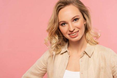 Blondine mit Zahnspange lächelt vereinzelt in die Kamera