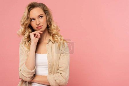 Photo pour Femme blonde pensive avec la main sur le menton isolé sur rose - image libre de droit