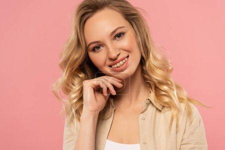 Lächelnde blonde Frau mit Hand am Kinn, isoliert auf rosa