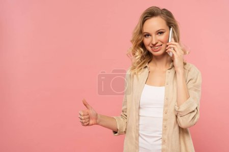 Photo for Smiling woman talking on smartphone and showing thumb up gesture isolated on pink - Royalty Free Image