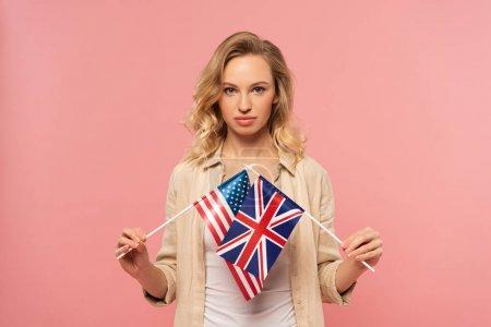 Photo pour Une jolie blonde tenant des drapeaux américain et britannique isolés sur le rose - image libre de droit