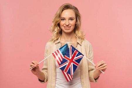 Photo pour Une femme blonde souriante tenant les drapeaux américain et britannique isolés sur le rose - image libre de droit