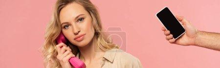 Foto de Mujer hablando por teléfono y mano de teléfono inteligente aislado en rosa, tiro panorámico - Imagen libre de derechos