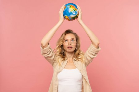 Photo pour Blonde woman holding globe above head isolated on pink - image libre de droit