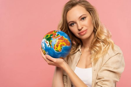 Photo pour Smiling blonde woman holding globe isolated on pink - image libre de droit