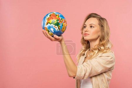 Photo pour Femme blonde tenant le globe dans la main isolée sur rose - image libre de droit