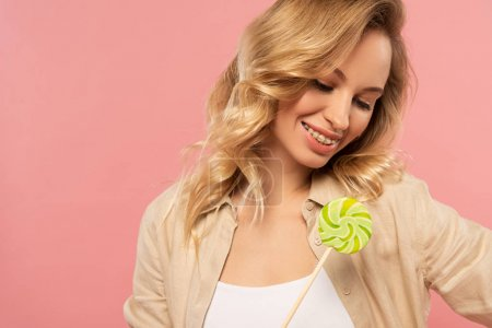 Photo for Smiling blonde woman looking at lollipop isolated on pink - Royalty Free Image
