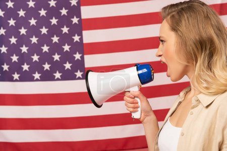 Photo for Young woman screaming in loudspeaker with american flag at background - Royalty Free Image