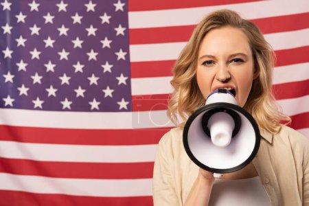 Photo pour Jeune femme criant dans un haut-parleur avec un drapeau américain en arrière-plan - image libre de droit