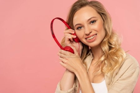 Smiling blonde woman listening headphone isolated on pink
