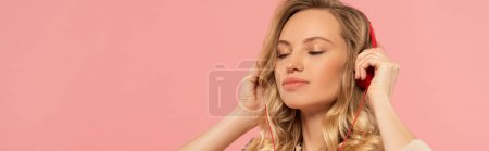 Blonde woman with closed eyes in headphone isolated on pink, panoramic shot