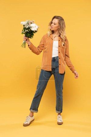 Photo pour Belle femme blonde tenant bouquet sur fond jaune - image libre de droit