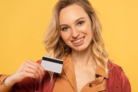 Photo pour Femme souriante tenant la carte de crédit isolée sur jaune - image libre de droit