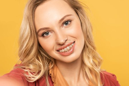 Camera point of view of smiling woman with dental braces taking selfie isolated on yellow