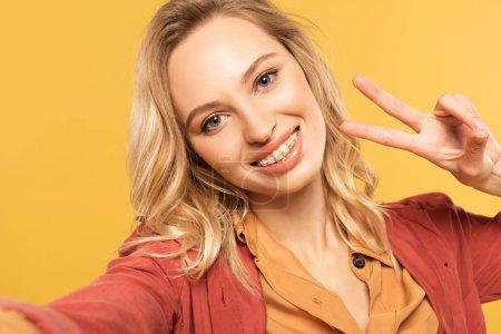 Photo pour Femme souriante avec des appareils dentaires montrant un signe de paix tout en prenant selfie isolé sur jaune - image libre de droit