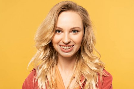Portrait of smiling blonde woman isolated on yellow