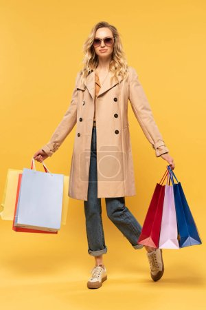 Photo pour Femme blonde en lunettes de soleil tenant des sacs à provisions sur fond jaune - image libre de droit
