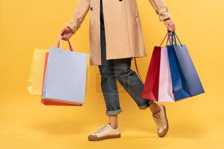 Photo pour Vue recadrée de la femme tenant des sacs à provisions dans les mains sur fond jaune - image libre de droit