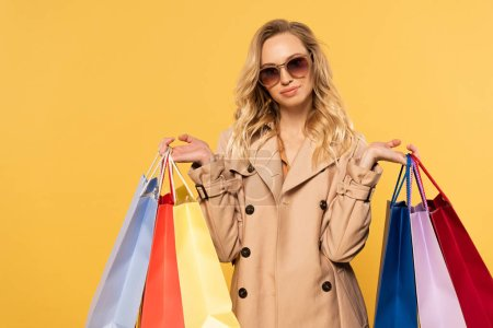 Photo for Blonde woman in sunglasses holding shopping bags in hands isolated on yellow - Royalty Free Image