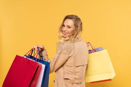 Photo pour Smiling blonde woman holding shopping bags in hands isolated on yellow - image libre de droit