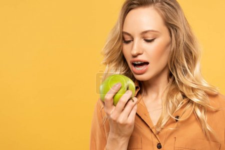 Young woman with dental braces biting green apple isolated on yellow